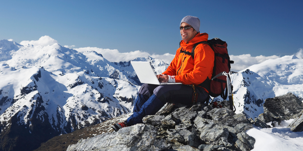 Man working remotely on a mountaintop