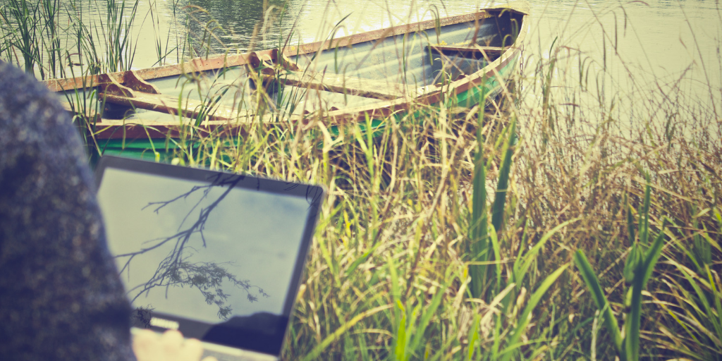 Man working remotely in nature by a boat