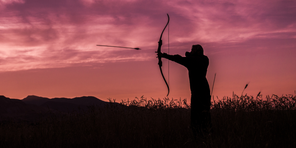 Silhouette of archer in crimson evening sky