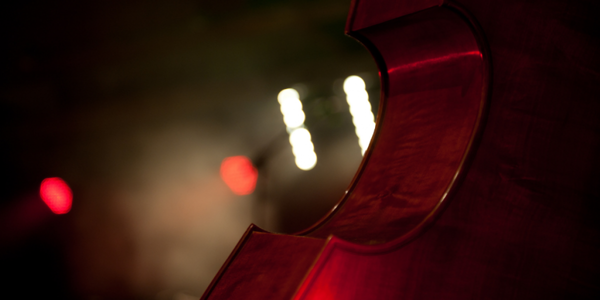 Part of a cello with blurry lights in background