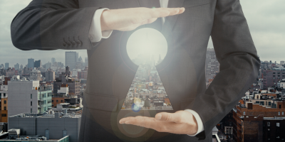 Man in business suit holding abstract keyhole that you can see through