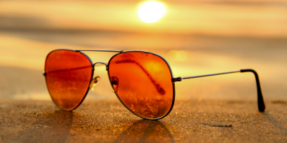 Orange sunglasses on the sand with sun shining behind them