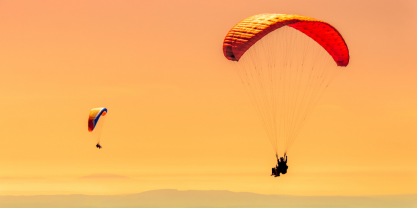 Two paragliders in sunlight