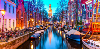 Picturesque Amsterdam in colorful lights with bikes, canal & cathedral