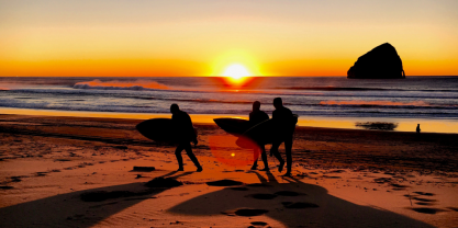 Three surfers leaving the beach at sunset