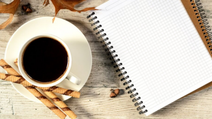 Coffee mug with wafers & open notebook on an autumn-flavored desk