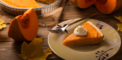Slice of pumpkin pie with cream on plate and cut up pumpkin next to it