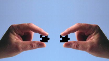 Two hands holding puzzle pieces that fit