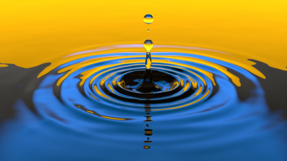 Drop falling into still water and creating ripples