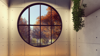 Room with a circular window with bars looking out at trees outside