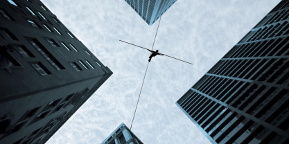 Acrobat balancing on a rope between tall buildings