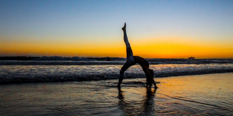 Woman doing yoga on a beach at sunset