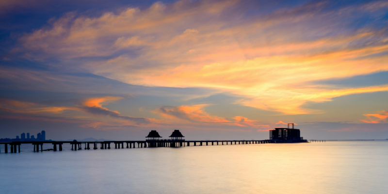 Very long pier with calm sea and orange clouds in the background