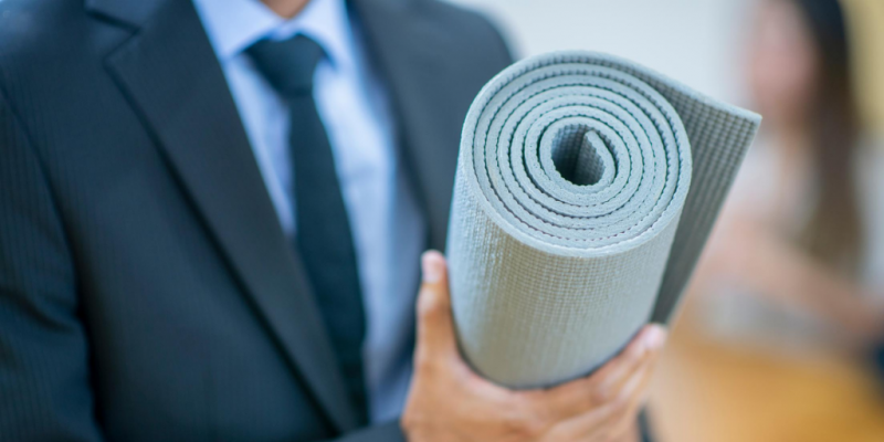 Man in business suit holding rolled up yoga mat