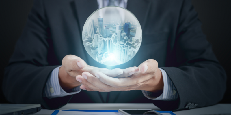 Hands holding crystal ball showing futuristic city