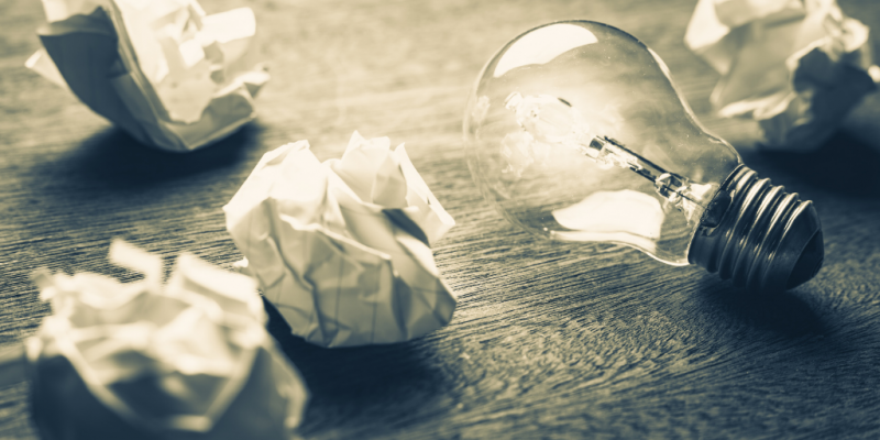 Lightbulb with several crinkled pieces of paper scattered around